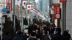 Shoppers Walk Down A Busy Street In The Ginza Shopping District