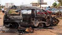 A Woman Walks Near A Minibus Burnt By An Angry Mob